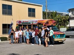 group shot in front of monkey bus at Waves, Wings, & Wheels event
